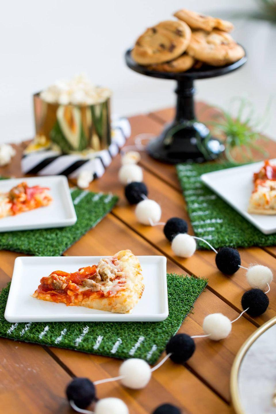 "<p>These budget-friendly placemats will make your guests feel like they're really getting in on the action. Plus, all you really need to make them is a little bit of astroturf, scissors, and white paint. </p><p><em><a href=""https://sugarandcloth.com/tailgate-tips-diy-football-coasters-placemats/"" rel=""nofollow noopener"" target=""_blank"" data-ylk=""slk:Get the tutorial at Sugar and Cloth »"" class=""link rapid-noclick-resp"">Get the tutorial at Sugar and Cloth »</a></em></p><p><a class=""link rapid-noclick-resp"" href=""https://www.amazon.com/Juvale-Artificial-Grass-Synthetic-Non-Slip/dp/B07F28DZ8F?tag=syn-yahoo-20&ascsubtag=%5Bartid%7C10055.g.4949%5Bsrc%7Cyahoo-us"" rel=""nofollow noopener"" target=""_blank"" data-ylk=""slk:SHOP ASTROTURF PATCHES"">SHOP ASTROTURF PATCHES</a><em><br></em></p>"