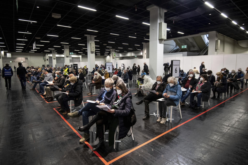 People wait with mouth-to-nose coverage in a vaccination center in Cologne, Germany, Sunday, April 4, 2021. In North Rhine-Westphalia, people aged 60 and over have been able to get vaccinated against the coronavirus with the active ingredient from Astrazeneca since this weekend. The rush for the vaccination appointments for the age group 60 plus had already led to overloaded lines on the phone and on the Internet in the early morning of Holy Saturday, 03.04.2021. (Marius Becker/dpa via AP)