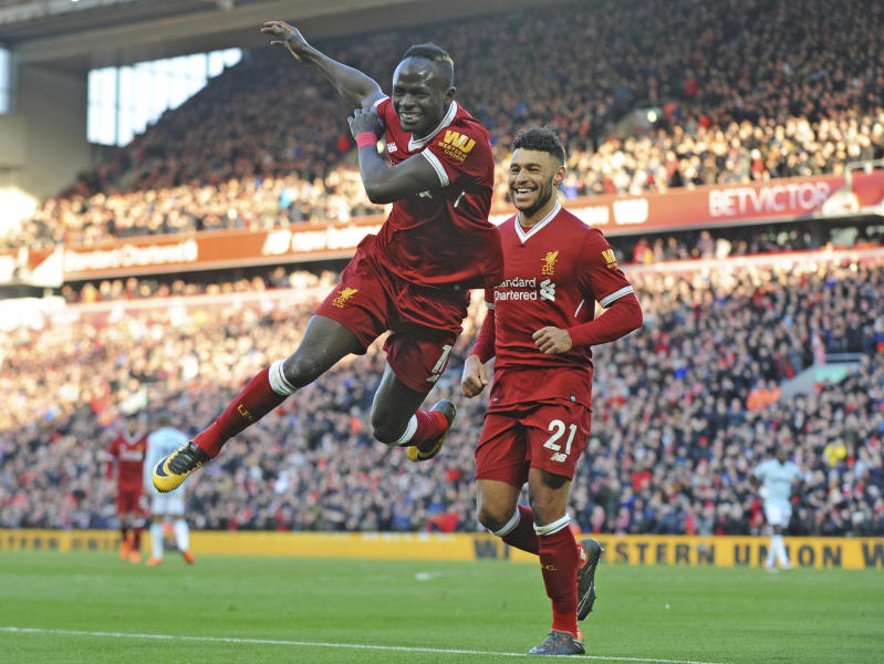 Liverpool's Sadio Mane, left, celebrates scoring his sides fourth goal during the English Premier League soccer match between Liverpool and West Ham United at Anfield in Liverpool, England, Saturday, Feb. 24, 2018. (AP Photo/Rui Vieira)