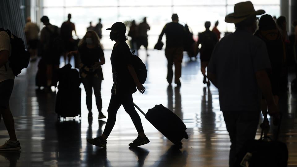 FILE - In this July 1, 2021, file photo, people travel through Salt Lake City International Airport in Salt Lake City. Americans enjoying newfound liberty are expected to travel and gather for cookouts, fireworks and family reunions over the Fourth of July weekend in numbers not seen since pre-pandemic days. (AP Photo/Rick Bowmer, File)