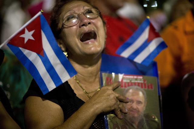<p>A woman holding a portrait of Cuban leader Fidel Castro cries moments after his funeral procession passes by in Bayamo, Cuba, Dec. 2, 2016. Castro's ashes were traveling on a four-day journey across Cuba, through small towns and cities where his rebel army fought its way to power nearly 60 years ago, to their final resting place in the eastern city of Santiago. (Photo: Rodrigo Abd/AP) </p>