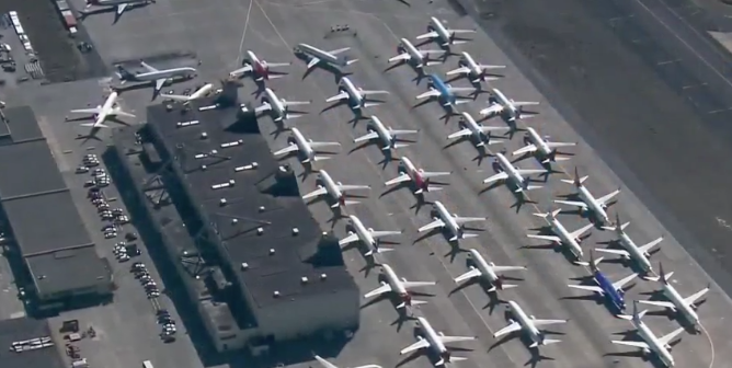 Dozens of aircraft parked at an airport as airlines suspend routes and passenger numbers plummet due to the coronavirus pandemic: NBC News