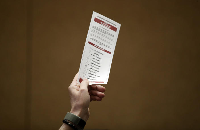 A man holds up a preference card with Democratic presidential candidate Sen. Bernie Sanders, I-Vt., marked, during a presidential caucus at the Bellagio hotel-casino, Saturday, Feb. 22, 2020, in Las Vegas. (AP Photo/John Locher)