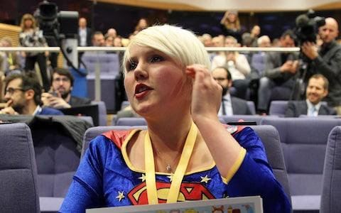 A pro-EU protester sits in the front row of the press conference before being escorted out