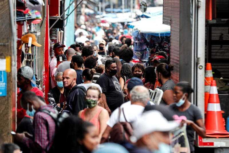 Dozens of people walk on a busy commercial street in the centre of Sao Paulo, Brazil.