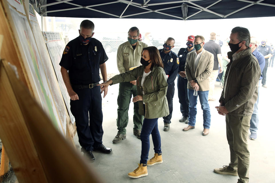 Mark Johnson, left, unit chief for Cal Fire in Fresno, watches Democratic vice presidential candidate Sen. Kamala Harris, D-Calif., and California Gov. Gavin Newsom are briefed on the damage during the Creek Fire at Pine Ridge Elementary, Tuesday, Sept. 15, 2020 in Auberry, Calif. (AP Photo/Gary Kazanjian)