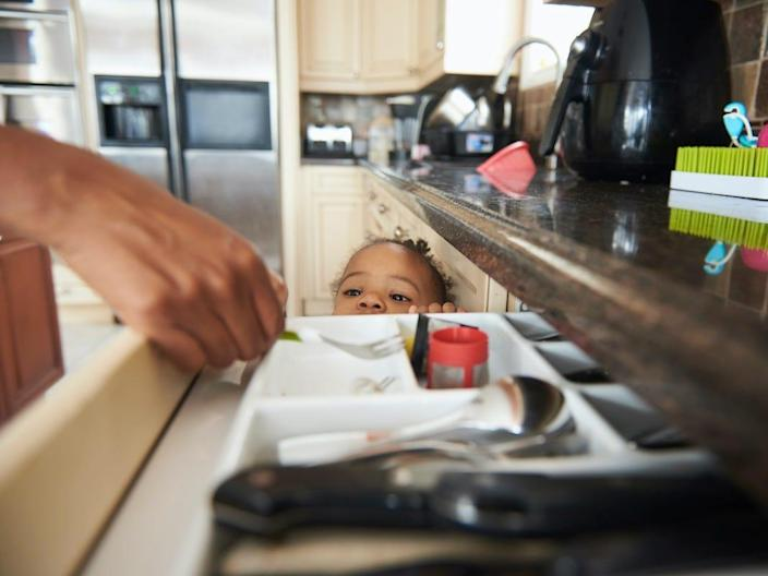 A child peers into a kitchen drawer.