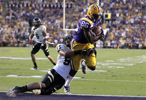 Idaho linebacker Homer Mauga (55) tries to tackle LSU wide receiver Kadron Boone (86) as he scores a touchdown on a pass play in the first half of their NCAA college football game in Baton Rouge, Saturday, Sept. 15, 2012. (AP Photo/Gerald Herbert)