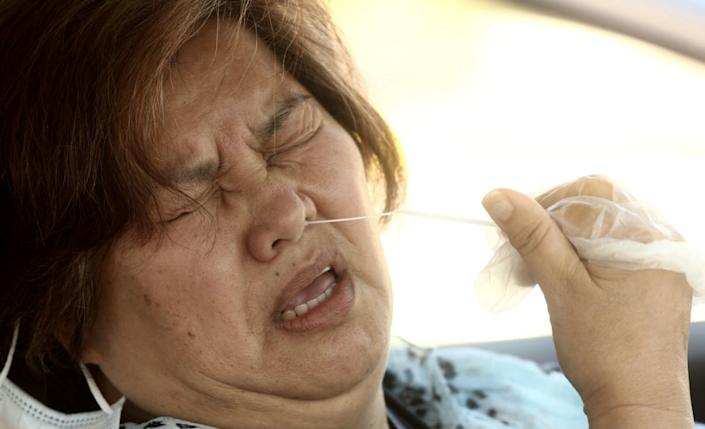 Paz Velasquez, 61, grimaces as she self-tests April 28 at a drive-up testing site for COVID-19 in Carson.