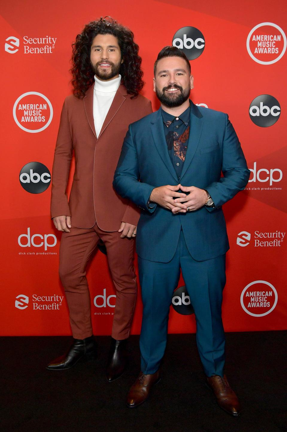 <p>Wearing jewel-toned suits.</p>