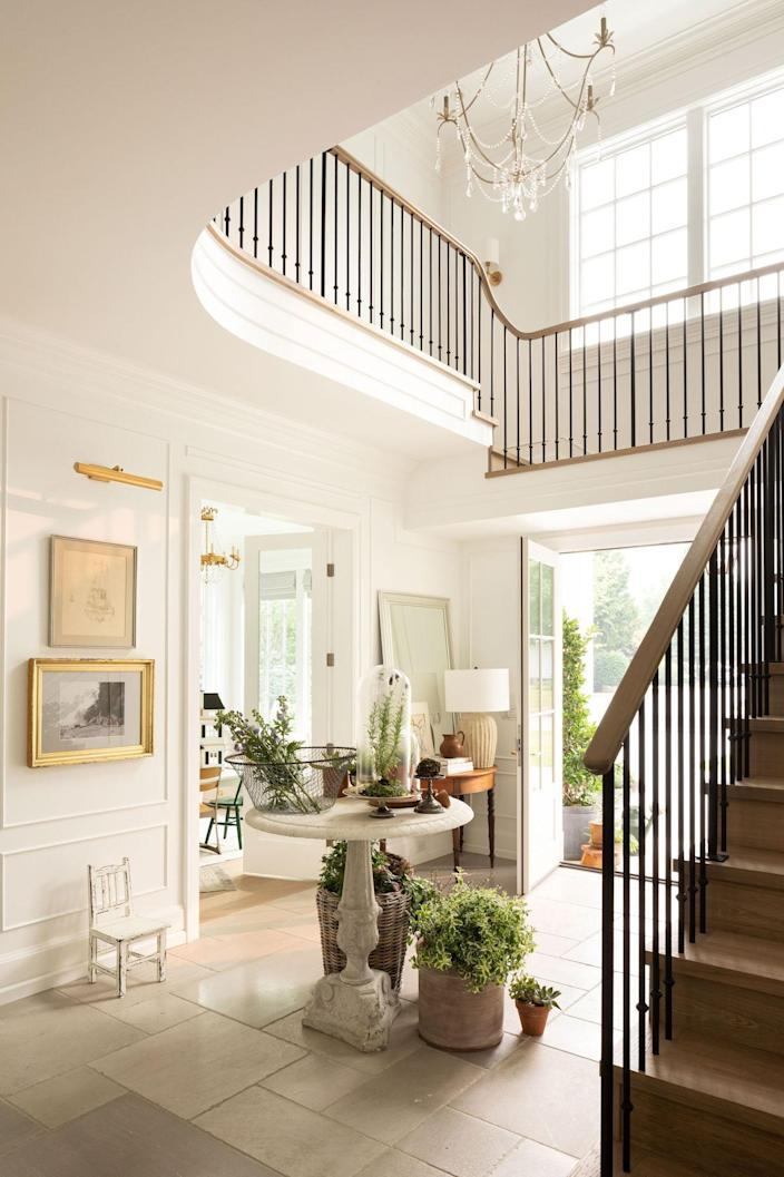 In the entry, guests are greeted with Adera Stone limestone tiles, a Currey and Company chandelier, railings by Alviar Woodworking, and a 19th-century Italian marble table by Scott Landon Antiques.