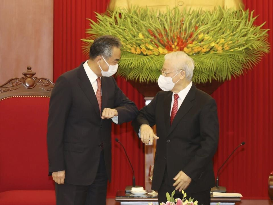 Vietnamese Communist Party General Secretary Nguyen Phu Trong and Chinese Foreign Minister Wang Yi elbow as they meet in Hanoi, Vietnam on Saturday, Sep.11, 2021. China has pledged to donate 3 million doses of its vaccine to Vietnam as Wang closed his visit to Hanoi. (Le Tri Dung/VNA via AP)