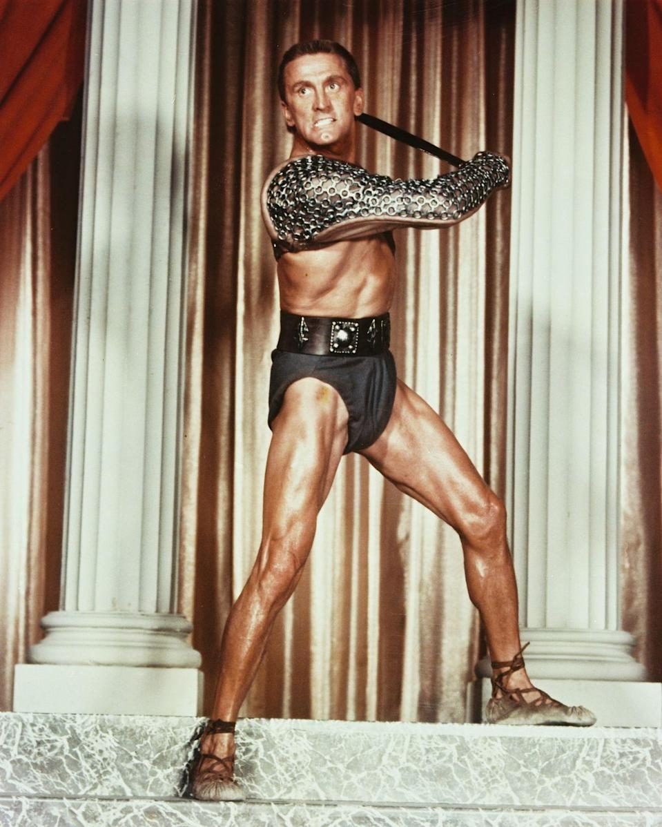<p>Kirk Douglas took flexing to a whole new level when he posed for this promotional photo for <em>Spartacus </em>in 1960. The actor played the lead character, a ripped gladiator named Thracian Spartacus, in the critically acclaimed hit. </p>
