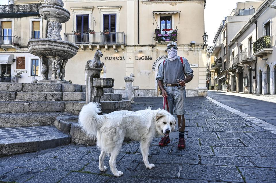 TAORMINA , ITALY - APRIL 08: A man wearing a protective mask walks his dog on April 08, 2020 in Taormina, Italy. There have been well over 100,000 reported COVID-19 cases in Italy and more than 15,000 related deaths, but the officials are confident the peak of new cases has passed. (Photo by Fabrizio Villa/Getty Images)