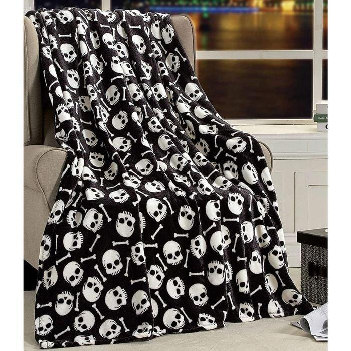 <p>The <span>Ultra Soft and Cozy Halloween Skulls and Webs Ultra Plush Throw Blanket</span> ($24, originally $40) is made with fleece fabric that's super comfortable. </p>