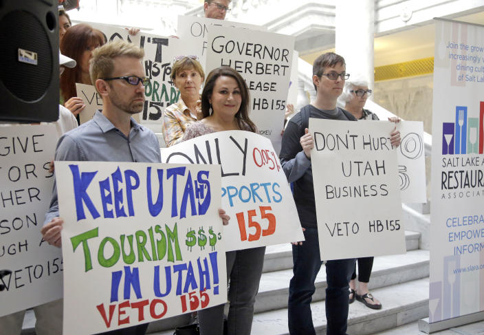 FILE - In this March 17, 2017, file photo, protesters holds signs during rally concerning the DUI threshold at the Utah state Capitol in Salt Lake City. New Year's Eve revelers in Utah may find themselves with more than a hangover as 2019 dawns: If they drink and drive, they could get hit by the newest and lowest DUI threshold in the nation. The .05 percent limit goes into effect Dec. 30, despite protests that it will punish responsible drinkers, hurt the state's tourism industry and amplify its alcohol-unfriendly reputation. (AP Photo/Rick Bowmer, File)