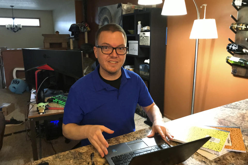 Brenton Nesemeier, who manages COVID-19 case managers and field managers at the North Dakota Department of Health, works at his home in Fargo, N.D., on Dec. 11, 2020. He said the state curtailed much of its contact tracing among the general public as the virus surged, and relying on people who test positive to tell anyone they were in close contact with. (Zachery Noble via AP)