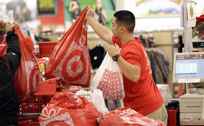 A Target employee hands bags to a customer at the register at a Target store in Colma, Calif., Friday, Nov. 23, 2012. Black Friday, the day when retailers traditionally turn a profit for the year, got a jump start this year as many stores opened just as families were finishing up Thanksgiving dinner. Stores are experimenting with ways to compete with online rivals like Amazon.com that can offer holiday shopping deals at any time and on any day. (AP Photo/Jeff Chiu)
