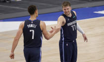Dallas Mavericks center Dwight Powell (7) and guard Luka Doncic (77) celebrate the team's 108-93 win over the Los Angeles Lakers following an NBA basketball game Saturday, April 24, 2021, in Dallas. (AP Photo/Ron Jenkins)