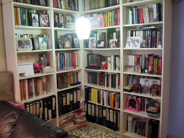 At one corner and along part of the walls in Dr Chee Soon Juan's house is a floor to ceiling bookcase filled with volumes and photographs of different members of the family. (Yahoo! photo/Jeanette Tan)