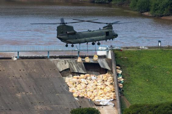 An RAF Chinook helicopter flies in sandbags to help repair the dam at Toddbrook Reservoir near Whaley Bridge (EPA)