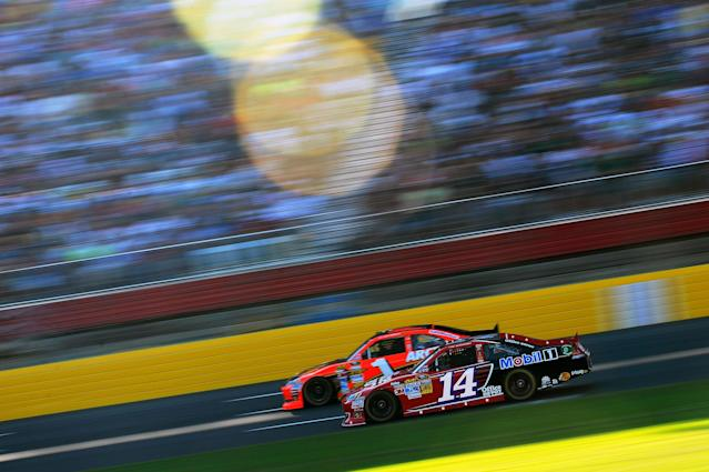 CONCORD, NC - MAY 27: Tony Stewart, driver of the #14 Office Depot/Mobil 1 Chevrolet, and Jamie McMurray, driver of the #1 Bass Pro Shops/Arctic Cat Chevrolet, race through the tri-oval during the NASCAR Sprint Cup Series Coca-Cola 600 at Charlotte Motor Speedway on May 27, 2012 in Concord, North Carolina. (Photo by Jared C. Tilton/Getty Images for NASCAR)