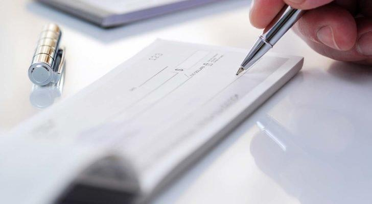 A hand holds a pen above a blank check.