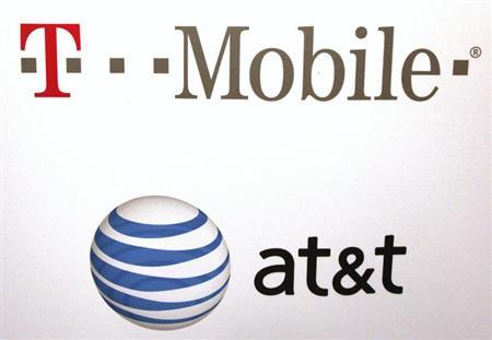 AT & T and T-Mobile logos are seen posted on the wall of a subway station at West 14th street and 8th avenue in New York