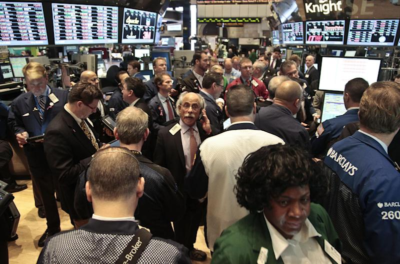 Traders crowd a a Barclays booth during early trading on the floor of the New York Stock Exchange on Tuesday, Nov. 20, 2012. Stocks sank early Tuesday on Wall Street. Hewlett-Packard stock suffered a big decline after its executives said that a company HP bought for $10 billion last year lied about its finances. (AP Photo/Bebeto Matthews)