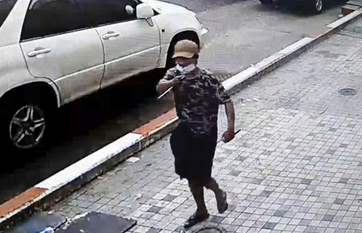 In this image taken from video obtained by Than Lwin Khet News, a man holds a pointed instrument before he attacks an unidentified man on the sidewalk of Sule Pagoda Road in Yangon, Myanmar, Thursday, Feb. 25, 2021. Members of a group supporting Myanmar's military junta have attacked and injured people protesting against the army's Feb. 1 seizure of power that ousted the elected government of Aung San Suu Kyi. (Than Lwin Thet News via AP)