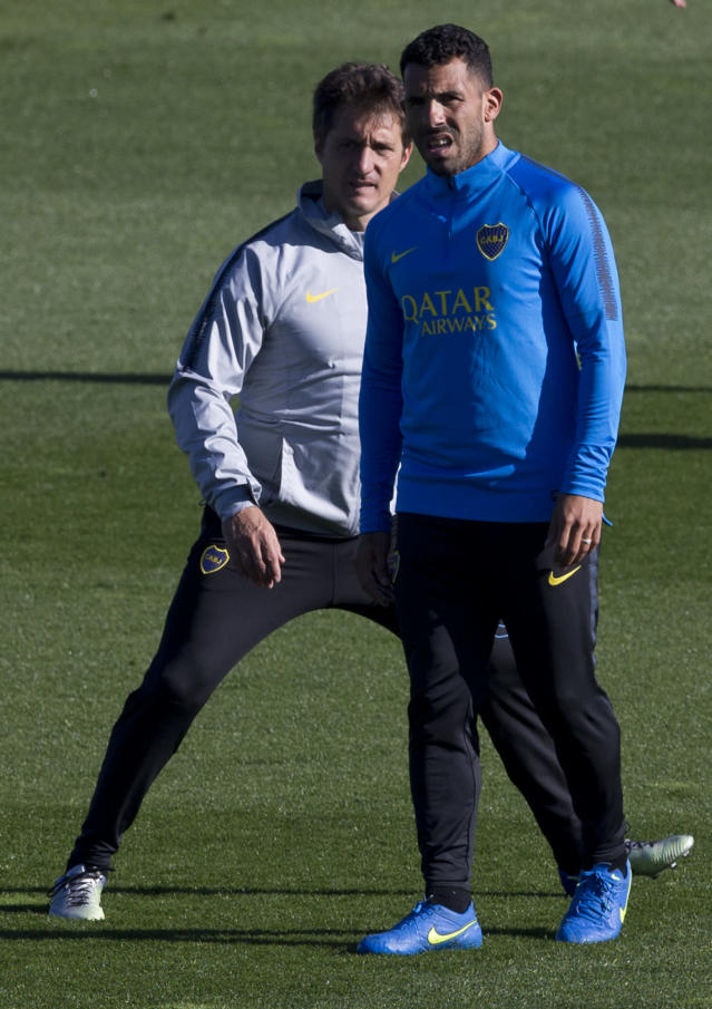 Boca Junior's coach Guillermo Barros Schelotto, left, stands behind Carlos Tevez during a training session in Madrid, Spain, Thursday, Dec. 6, 2018. The Copa Libertadores Final will be played on Dec. 9 in Spain at Real Madrid's stadium for security reasons after River Plate fans last Saturday attacked the Boca Junior team bus heading into the Buenos Aires stadium for the meeting of Argentina's fiercest soccer rivals. (AP Photo/Paul White)