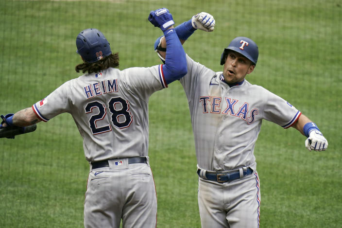 Texas Rangers' Nate Lowe, right, celebrates his home run with Jonah Heim during the eighth inning of a baseball game against the Los Angeles Angels, Wednesday, April 21, 2021, in Anaheim, Calif. (AP Photo/Jae C. Hong)