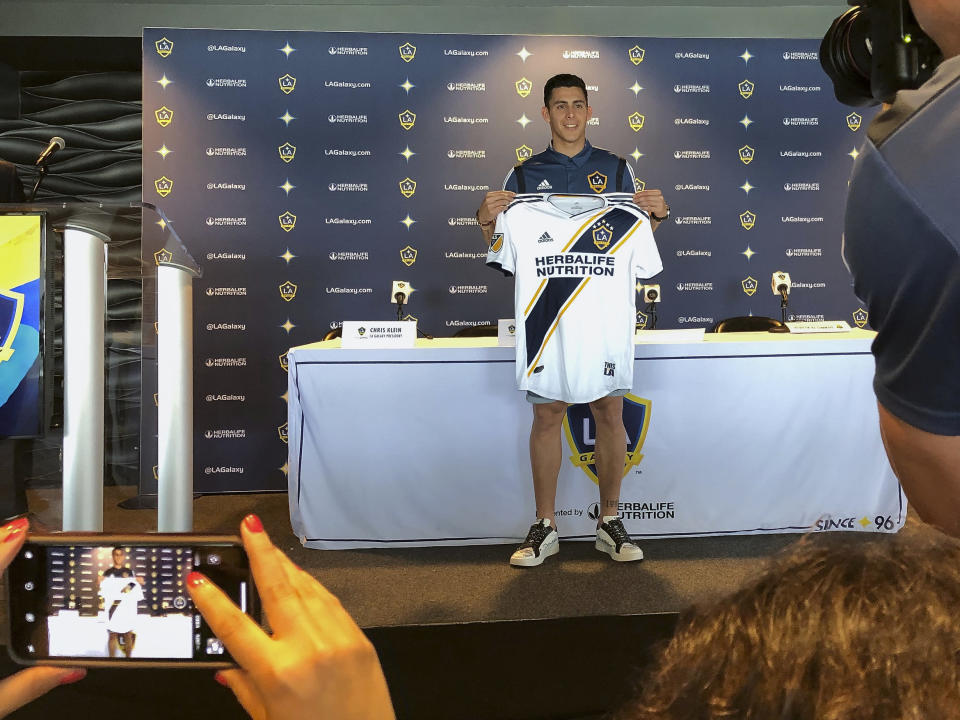 Forward Cristian Pavn of Argentina, holds up his new LA Galaxy jersey as he is introduced to the media at Dignity Health Sports Park in Carson, Calif., Thursday, Aug. 8, 2019. The LA Galaxy acquired Pavn on loan from Argentina's Boca Juniors this week in one of the biggest player acquisitions in recent Major League Soccer history. (AP Photo/Greg Beacham)