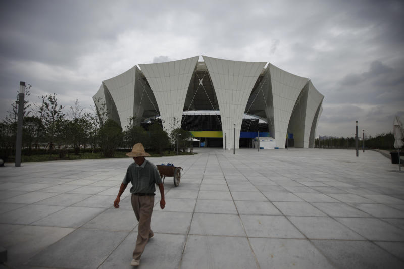 A worker walks near the outdoor diving pool Wednesday, July 13, 2011 at Shanghai Oriental Sports Center in Shanghai, China, ahead of the 14th FINA World Swimming Championships,  which start from July 16. (AP Photo/Eugene Hoshiko)