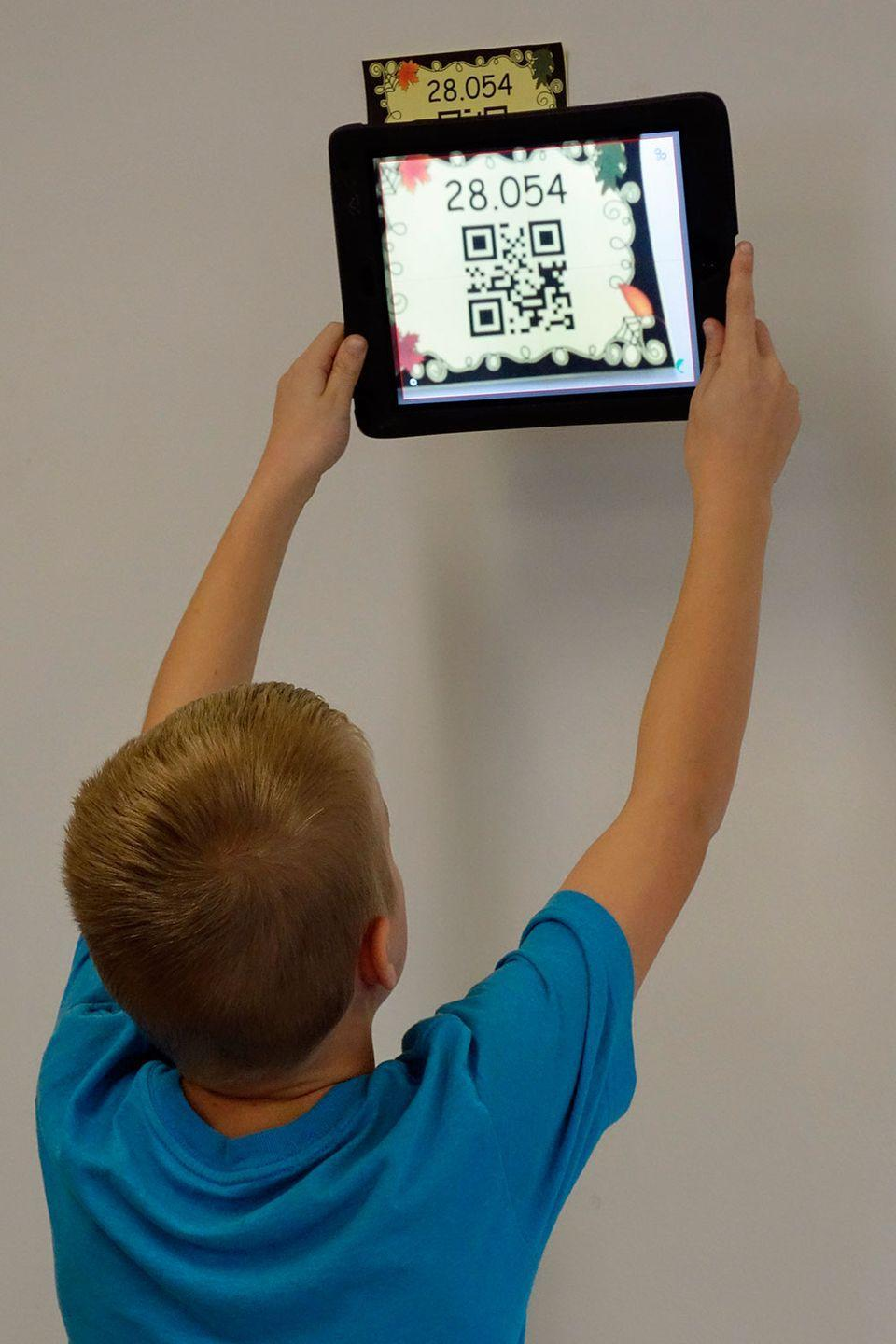 <p>A student uses an iPad to scan a QR code during an exercise in math class. </p>