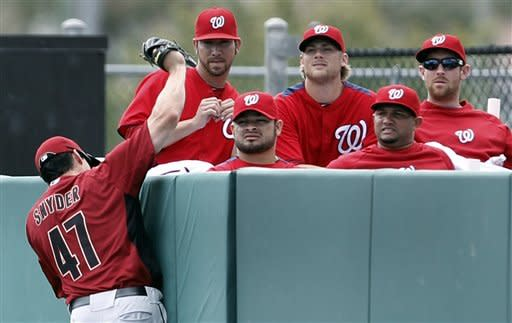 Houston Astros left fielder Brad Snyder (47) catches a Washington Nationals' Jason Michaels fly ball near the Nationals bullpen during a spring training baseball game in Viera Thursday, March 8, 2012. (AP Photo/Paul Sancya)