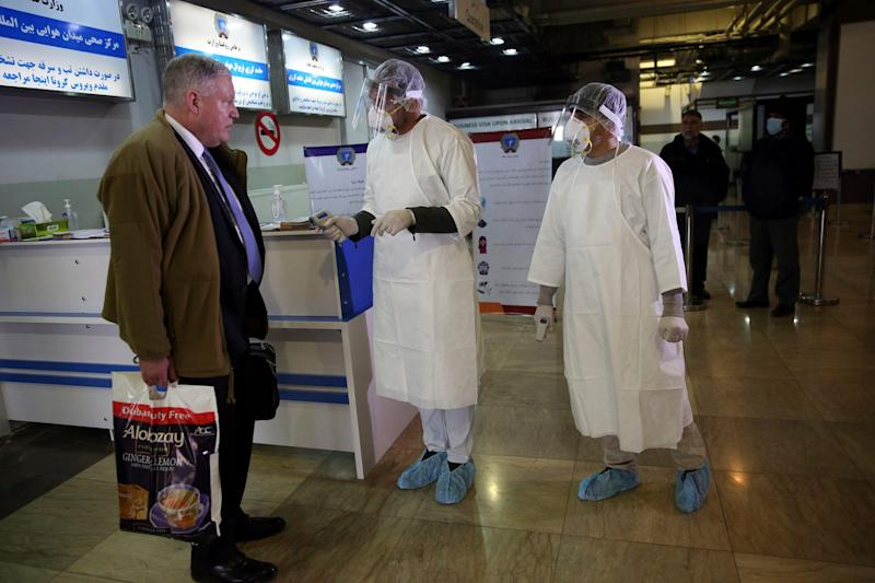 Afghan health workers wearing protective gear talk to a passenger who arrived from China as a preventive measure for Coronavirus 2
