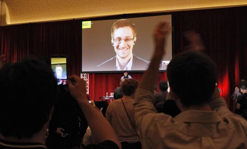 Supporters of Amnesty International cheer and shoot mobile phone videos as accused government whistleblower Snowden is introduced via teleconference during the Amnesty International Human Rights Conference 2014 in Chicago
