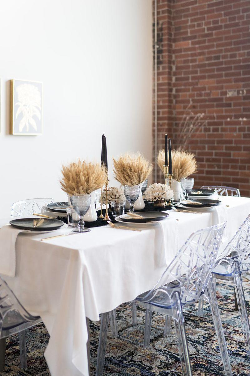 """<p>Just because your tablescape borders on """"glam"""" doesn't mean it can't still embody everything you love about country style. Black candles, brass candleholders, silver vases, and a bit of <a href=""""https://www.amazon.com/Wedding-Decorations-Sheaves-Natural-Centerpieces/dp/B07J9W4FZ9?tag=syn-yahoo-20&ascsubtag=%5Bartid%7C10050.g.2130%5Bsrc%7Cyahoo-us"""" rel=""""nofollow noopener"""" target=""""_blank"""" data-ylk=""""slk:dried wheat"""" class=""""link rapid-noclick-resp"""">dried wheat</a> join forces to create a look that's cosmopolitan-chic—but still imbued with the down-home charm you love.</p><p><strong>Get the tutorial at <a href=""""https://patternsandprosecco.com/thanksgiving-tablescape/"""" rel=""""nofollow noopener"""" target=""""_blank"""" data-ylk=""""slk:Patterns and Prosecco"""" class=""""link rapid-noclick-resp"""">Patterns and Prosecco</a>.</strong></p><p><strong><a class=""""link rapid-noclick-resp"""" href=""""https://www.amazon.com/Mega-Candles-Unscented-Receptions-Celebrations/dp/B00MYL6IRW?tag=syn-yahoo-20&ascsubtag=%5Bartid%7C10050.g.2130%5Bsrc%7Cyahoo-us"""" rel=""""nofollow noopener"""" target=""""_blank"""" data-ylk=""""slk:SHOP BLACK TAPER CANDLES"""">SHOP BLACK TAPER CANDLES</a><br></strong></p>"""