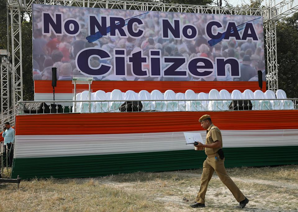 A policeman walks past a hoarding at the venue of a protest rally against a new citizenship law in Kolkata, India December 20, 2019. REUTERS/Rupak De Chowdhuri