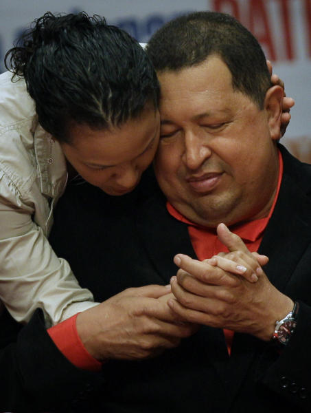 Venezuela's President Hugo Chavez, right, shares a moment with his daughter Rosa as he attends a concert in his honor at the Teresa Carreno theater in Caracas, Venezuela, Thursday, Feb. 23, 2012. Chavez is headed to Cuba for surgery Friday to remove a potentially cancerous tumor while the nation's congress on Thursday unanimously approved permission for Chavez to leave, a formality required by the nation's constitution. (AP Photo/Fernando Llano)