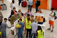Passengers talk to Civil Aviation Authority employees at Mallorca Airport as an announcement is expected on the Thomas Cook's tour operator, in Palma de Mallorca