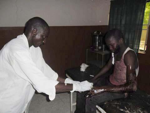In this photo taken with a mobile phone a doctor attends to a student from Government Secondary School in Mamudo, at the Potiskum General Hospital, Nigeria, following an attack by gunmen on Saturday July 6, 2013. Islamic militants attacked a boarding school before dawn Saturday, dousing a dormitory in fuel and lighting it ablaze as students slept, survivors said. At least 30 people were killed in the deadliest attack yet on schools in Nigeria's embattled northeast. (AP Photo/Adamu Adamu)