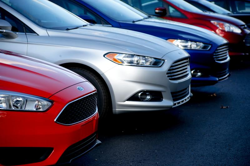 FILE- In this Nov. 19, 2015, photo, a row of new Ford Fusions are for sale on the lot at Butler County Ford in Butler, Pa. Under pressure from U.S. regulators, Ford is recalling nearly 1.4 million midsize cars in North America because the steering wheels can detach from the steering column and drivers could lose control. The recall covers certain Ford Fusion and Lincoln MKZ cars from the 2014 through 2018 model years. (AP Photo/Keith Srakocic, File)