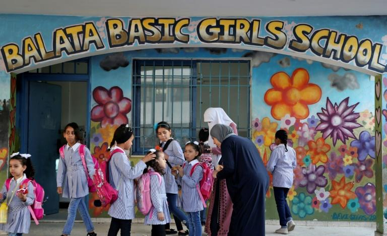 Pupils and teachers gather in front of a school run by UNRWA in Balata refugee camp, east of Nablus in the occupied West Bank on August 29, 2018