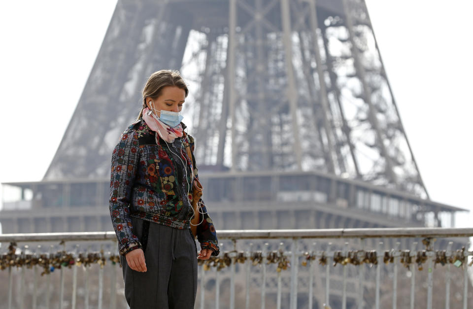 A woman is a mask in front of the Eiffel Tower in Paris. Source: Getty