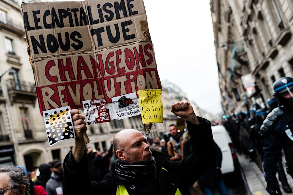 A demonstrator carries a sign reading 'Capitalism is killing us!' at a pension-reform strike in Paris on 9 January