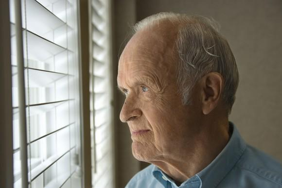 Older man looking out a window