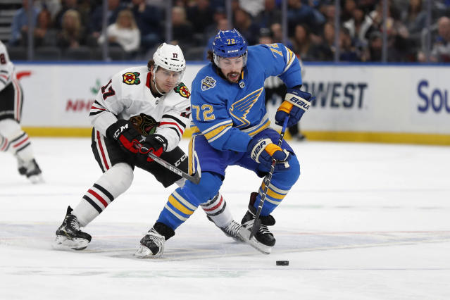 St. Louis Blues' Justin Faulk (72) controls the puck as Chicago Blackhawks' Dylan Strome defends during the first period of an NHL hockey game Saturday, Dec. 14, 2019, in St. Louis. (AP Photo/Jeff Roberson)