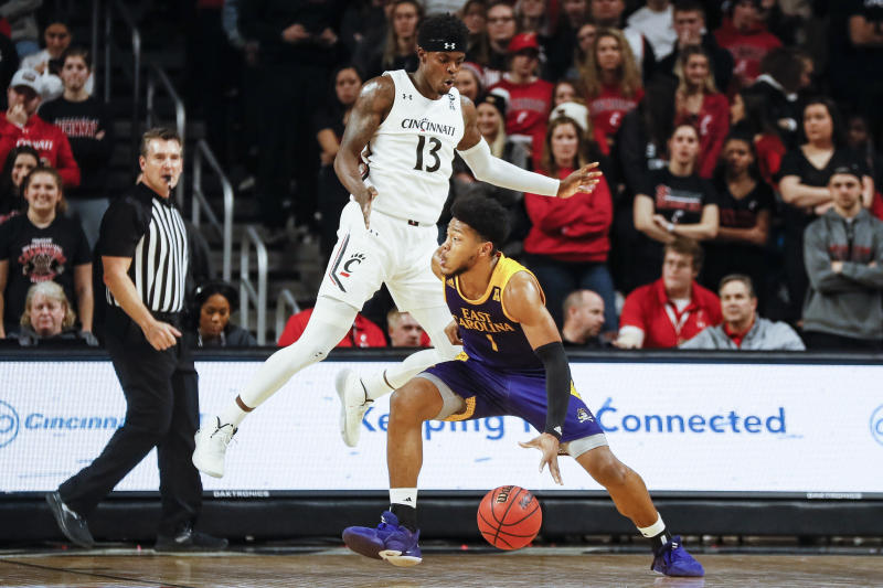 East Carolina's Jayden Gardner (1) looks to pass around Cincinnati's Tre Scott (13) during the first half of an NCAA college basketball game, Sunday, Jan. 19, 2020, in Cincinnati. (AP Photo/John Minchillo)